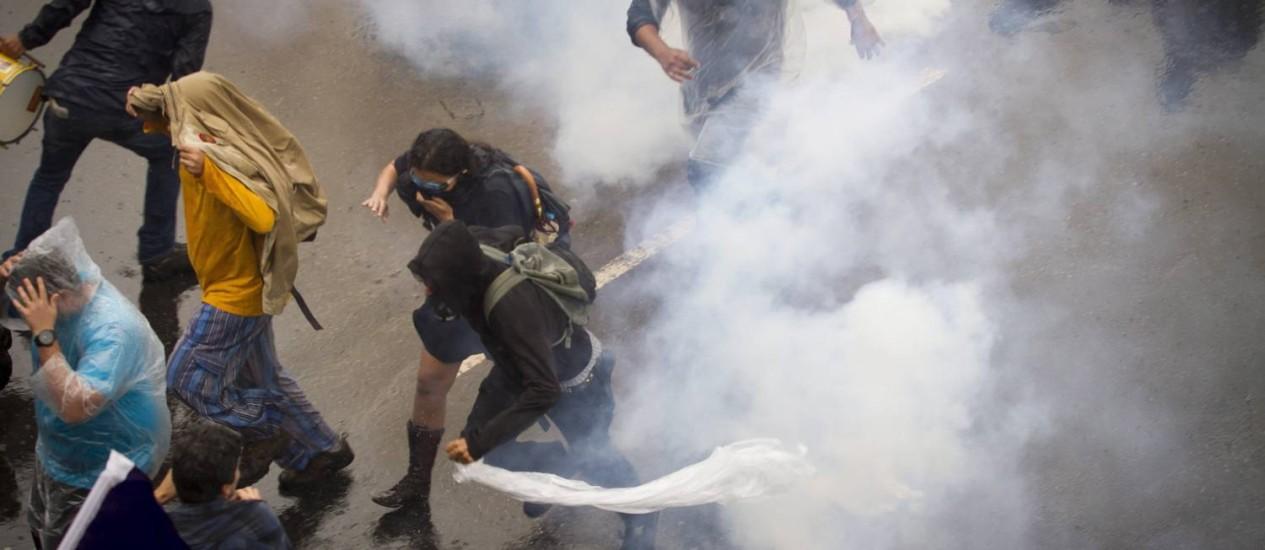 Professores em greve tentam se proteger de bomba de gás lançada por PMs durante protesto na Avenida Presidente Vargas Foto: Alexandro Auler / Agência O Globo