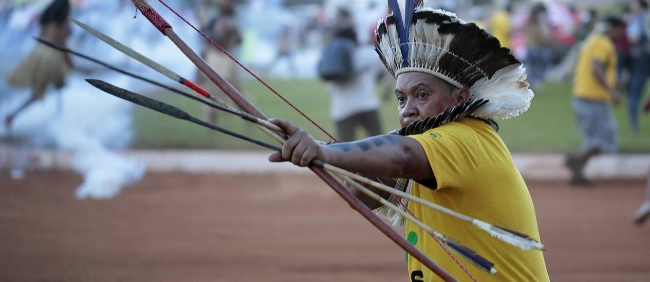 Um índio aponta o arco e flecha durante a manifestação em Brasília: confronto com a polícia Foto: REUTERS/Joedson Alves