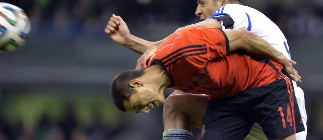 O atacante mexicano Javier Hernandez salta para a bola com Tal Ben, de Israel, durante amistoso no estádio Azteca Foto: OMAR TORRES / AFP