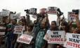 Em Bombaim, fotojornalistas seguram cartazes e câmeras em protesto contra estupro na Índia