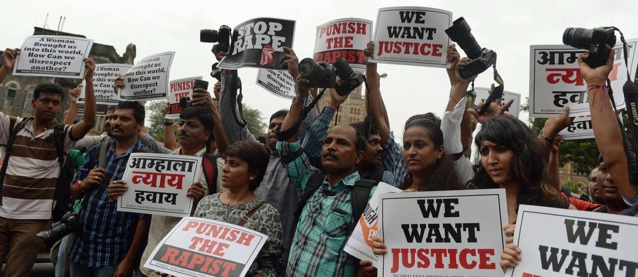 Em Bombaim, fotojornalistas seguram cartazes e câmeras em protesto contra estupro na Índia Foto: PUNIT PARANJPE / AFP