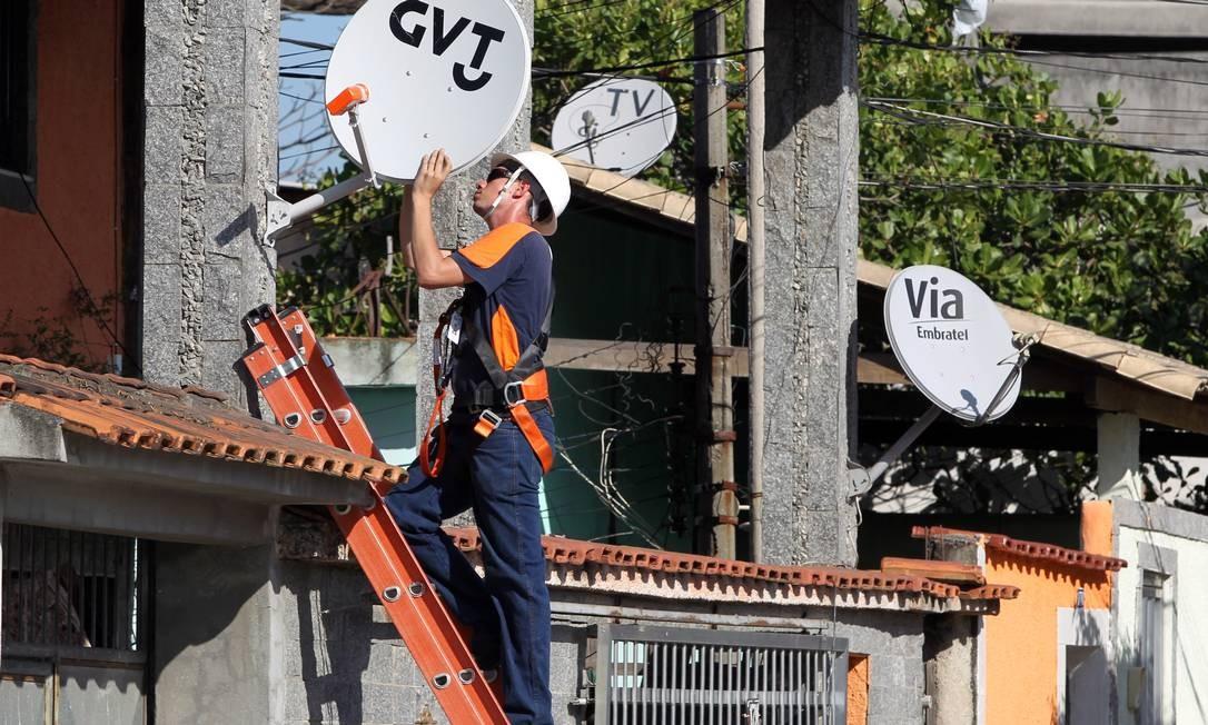 Funcionário da GVT instala a antena em Duque de Caxias, na Baixada Fluminense, onde começou a atuar com serviços de internet, telefone fixo e TV por assinatura Foto: / Carlos Ivan