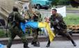 Combatentes pró-Moscou de Vostok rasgam uma bandeira ucraniana fora de um edifício da administração regional na cidade ucraniana de Donetsk