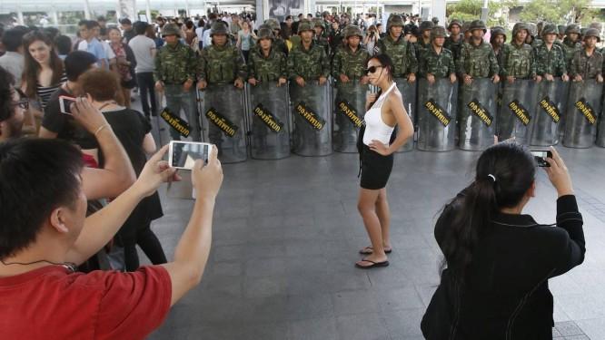 Uma menina posa para fotos diante de soldados, no Centro de Bangcoc Foto: ERIK DE CASTRO / REUTERS