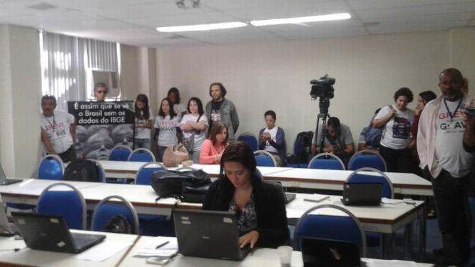 Ao fundo do auditório em que o PIB é divulgado, grevistas exibem faixas e camisetas contra a atual gestão do instituto Foto: O Globo / Lucianne Carneiro
