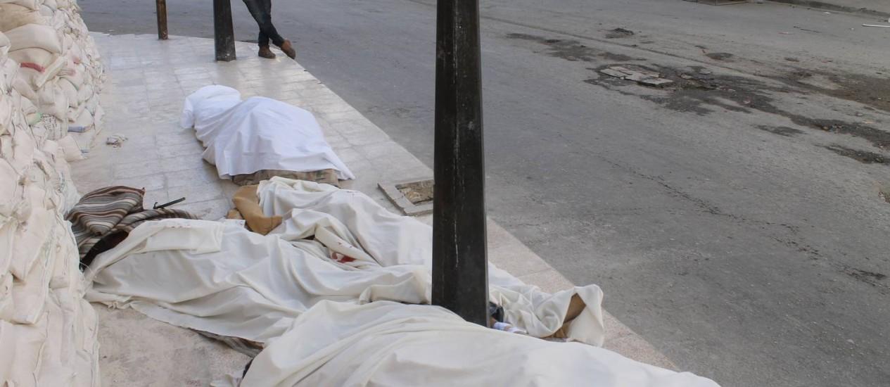 Corpos envoltos por panos são estendidos no chão em um bairro na cidade síria de Aleppo após um alegado ataque aéreo das forças do governo Foto: ZEIN AL-RIFAI / AFP