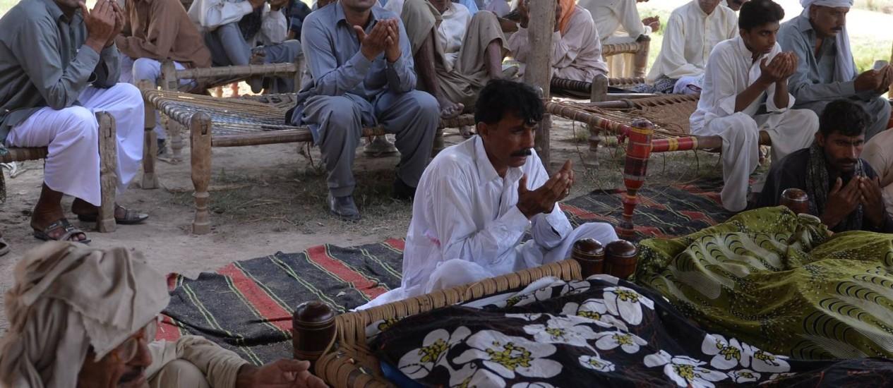 Residente paquistanês Mohammad Iqbal (centro) reza ao lado de parentes de sua esposa Farzana Parveen, que foi espancada até a morte com tijolos por seu pai e outros membros da família por se casar com um homem de sua própria escolha Foto: AAMIR QURESHI / AFP
