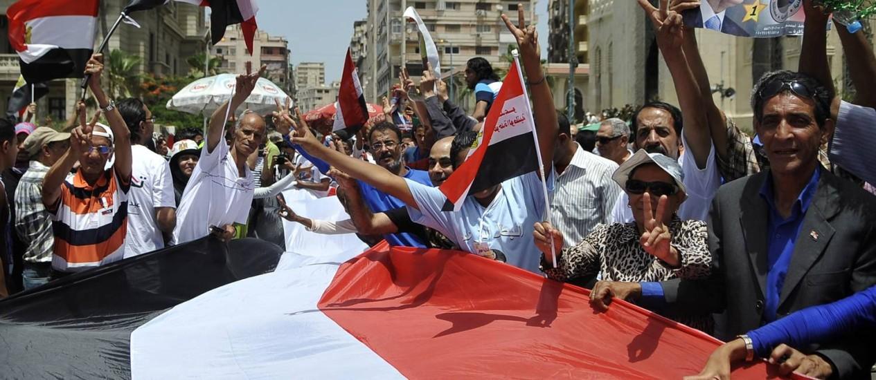 Simpatizantes do general Sisi levam cartazes e bandeiras durante uma passeata em Alexandria para comemorar sua vitória nas eleições presidenciais Foto: - / AFP