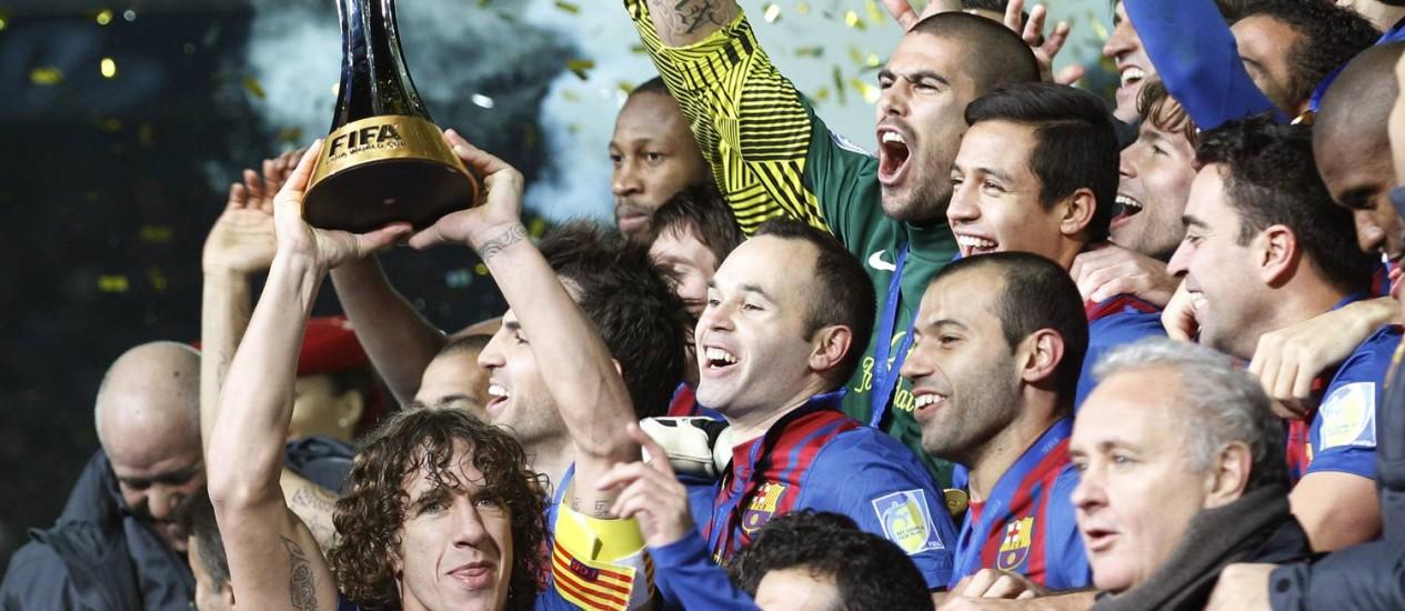 Puyol ergue a taça do Mundial de Clubes, em 2011: ex-zagueiro, ídolo da torcida, atuou por 15 anos no time do Barcelona Foto: Koji Sasahara / AP/Koji Sasahara