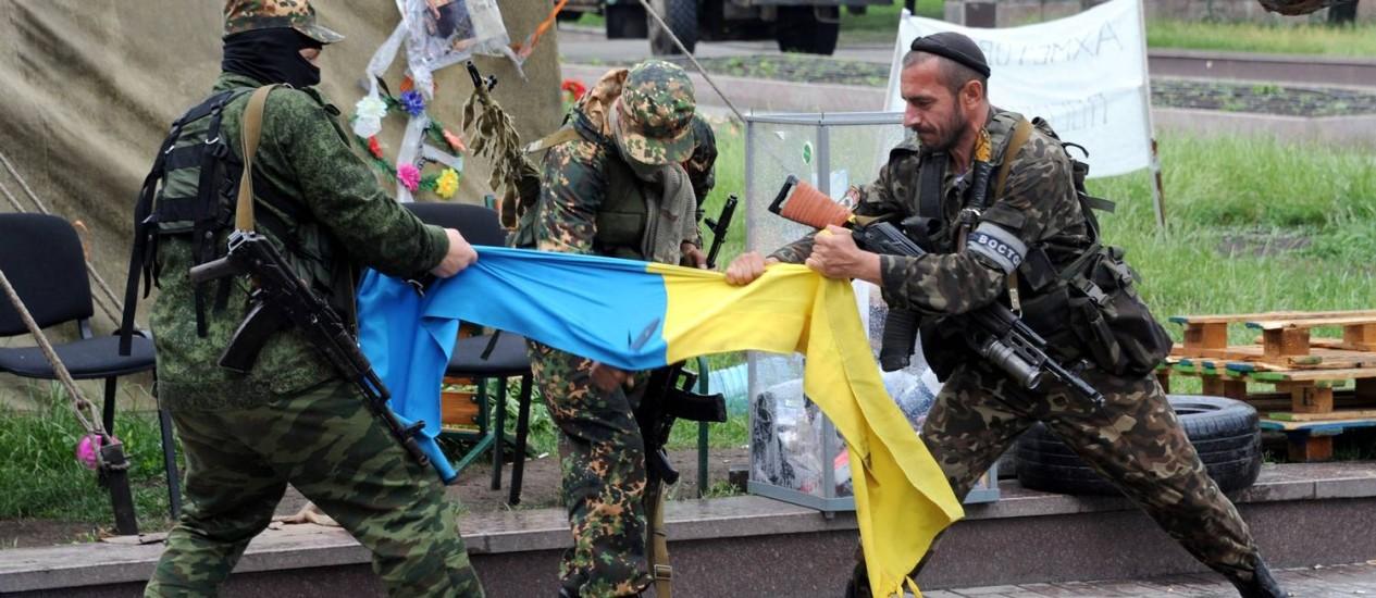 Rebeldes pró-Rússia rasgam bandeira ucraniana em Donetsk, no Leste da Ucrânia. Secretário-geral da Otan, Anders Fogh Rasmussen, afirmou nesta sexta-feira que cerca de dois terços de tropas na fronteira com a Ucrânia já começaram a retroceder, e pediu que Moscou deixe de apoiar os separatistas Foto: VIKTOR DRACHEV / AFP