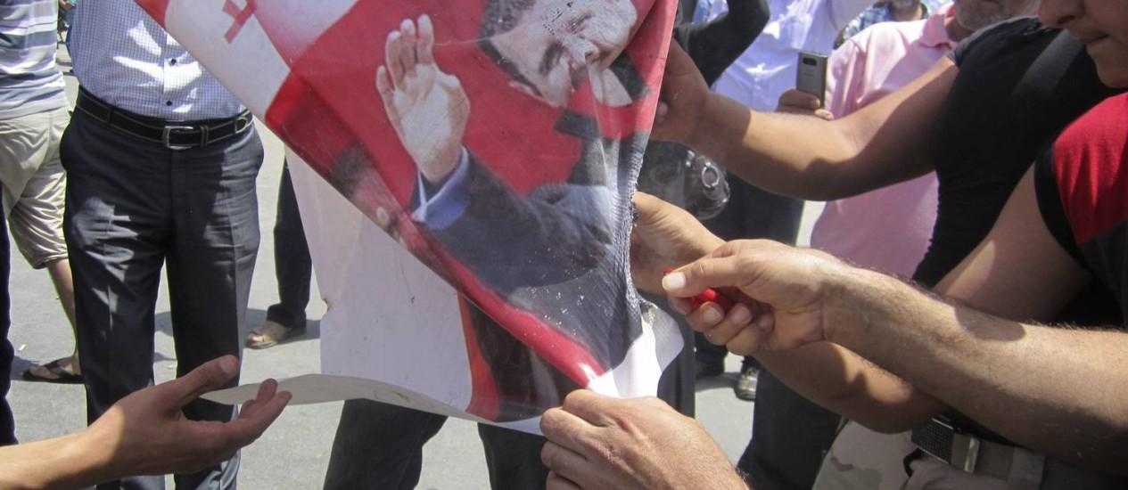 Libaneses e refugiados sírios contrários ao presidente queimar uma bandeira Foto: OMAR IBRAHIM/REUTERS