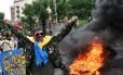Manifestantes da Praça da Independência de Kiev queimam pneus e tentam evitar que barricadas sejam desmontadas por serviços comunitários