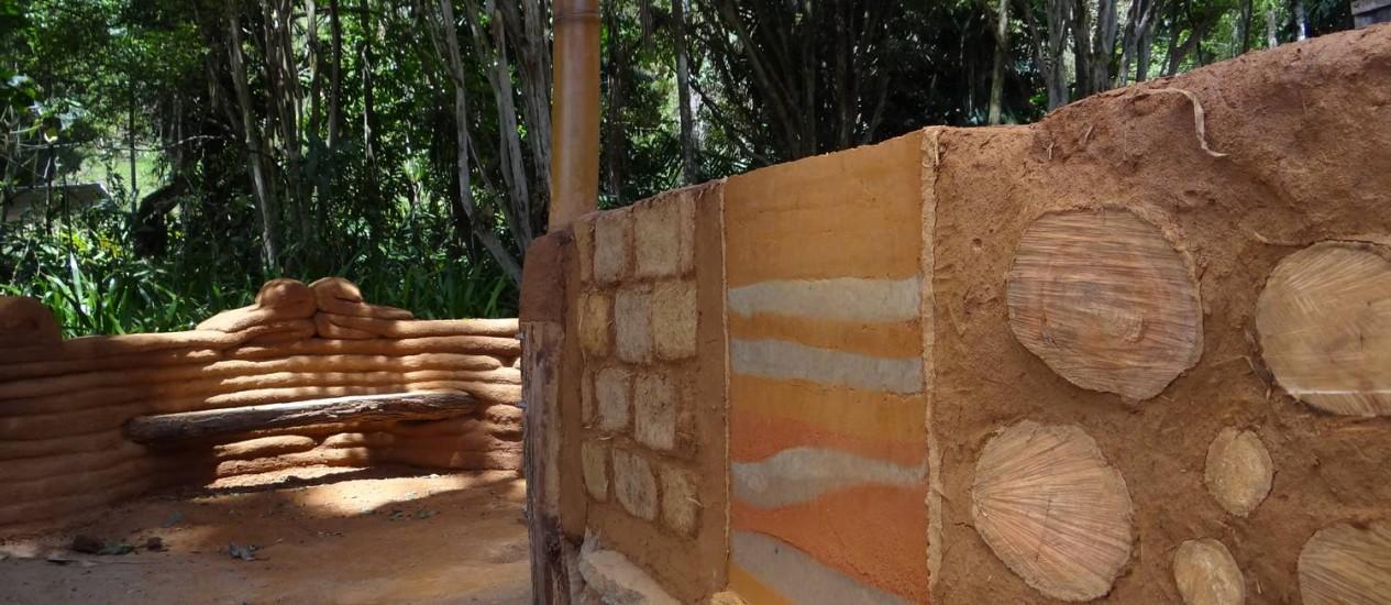 Quatro tipos de bioconstrução: ao fundo, o banco em superadobe; na parede, adobe, taipa de pilão e cordwood Foto: Divulgação