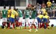 O mexicano Giovani dos Santos lamenta, enquanto, ao fundo, seu colega Luis Montes e o equatoriano Segundo Castillo são atendidos após dura dividida que tirou os dois da Copa do Mundo