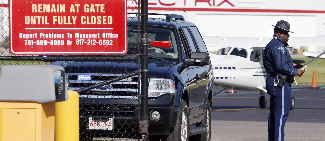 Um agente da polícia do estado de Massachusetts fica de guarda em um portão de entrada para a pista em Hanscom Foto: Michael Dwyer / AP