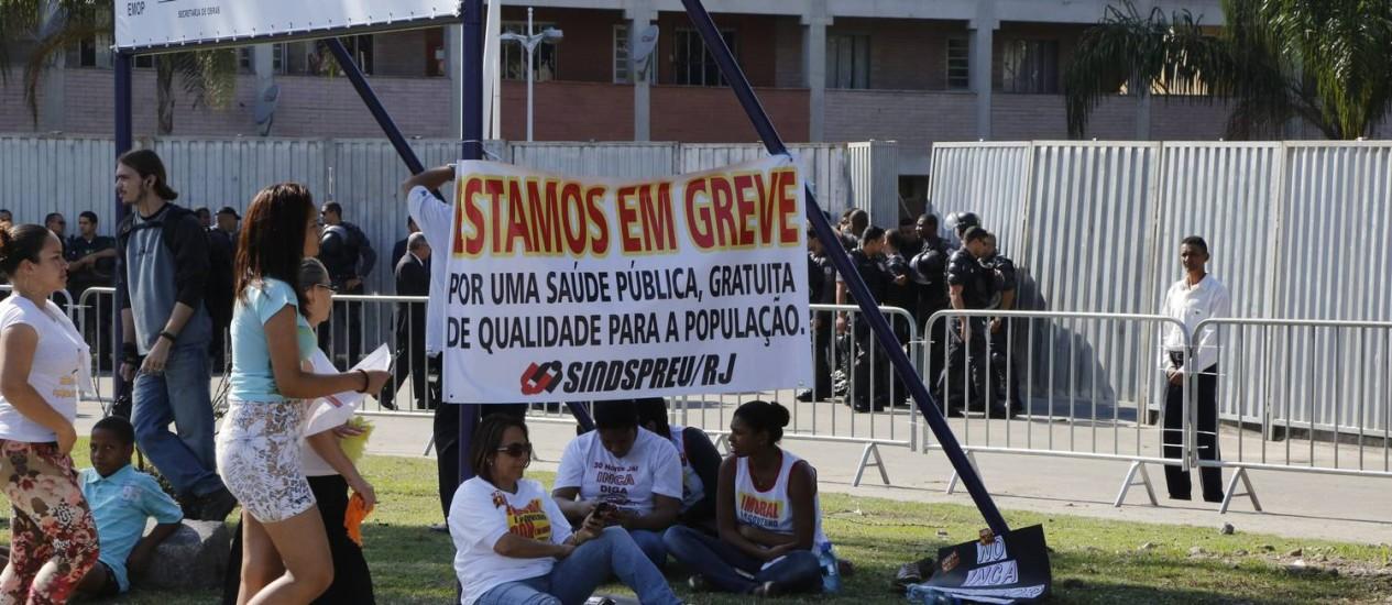 Funcionários da área de saúde mostram uma faixa enquanto esperavam a passagem de Dilma Rousseff, em Manguinhos Foto: Fabio Rossi / Agência O Globo