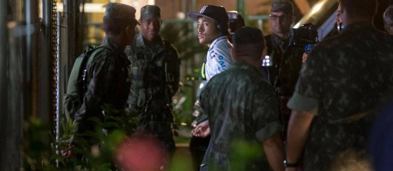 Cercado por soldados, Neymar entra no hotel da concentração da seleção brasileira em Goiânia Foto: Alexandre Cassiano