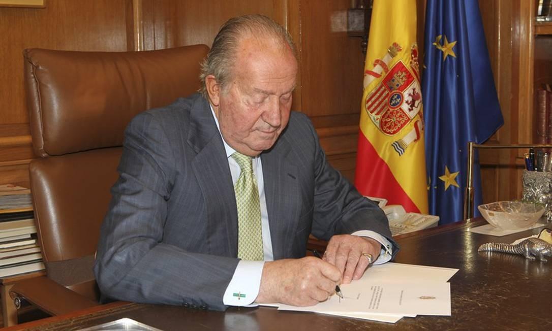 Em foto divulgada pelo governo espanhol, o rei Juan Carlos I assina sua abdicação ao trono Foto: AP