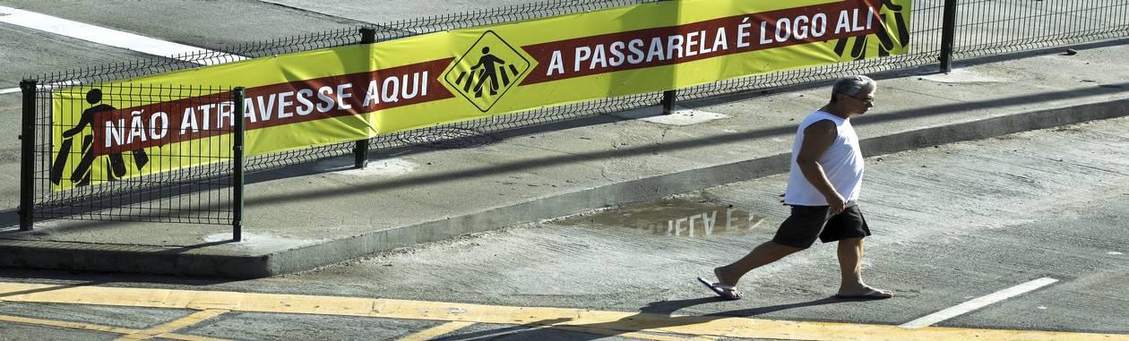 Pedestre atravessa em lugar proibido no primeiro dia de funcionamento do BRT Transcarioca Foto: Gabriel de Paiva / Agência O Globo
