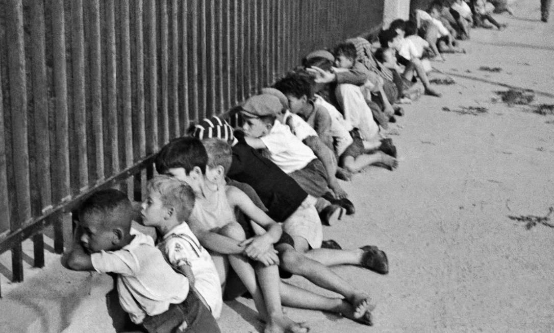 Suspensórios e boinas para meninos: na foto, garotos espiam, curiosos, o interior do estádio do Pacaembu, na década de 1940 Foto: Acervo Instituto Moreira Salles