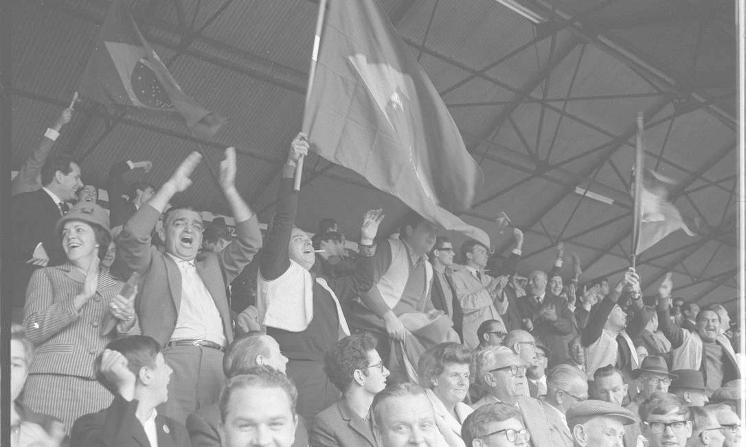 'Assim vemos que até as décadas de 1950 e 1960, os homens iam de ternos - o lenço no bolso era de ordem - aos estádios. Hoje, os torcedores exibem a moda dos seus ídolos', afirma Lula. Na foto, a torcida brasileira no primeiro jogo do Brasil na Copa do Mundo de 1966 contra a Bulgária que aconteceu em Liverpool Foto: José Santos / Agência O Globo