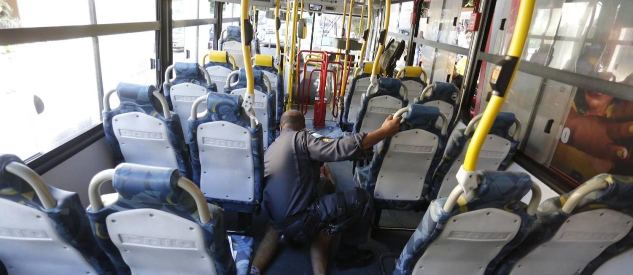 Policial Militar verifica homem que infartou e morreu dentro de ônibus em fernte ao Instituto Nacional de Cardiologia, em Laranjeiras Foto: Pablo Jacob / Pablo Jacob