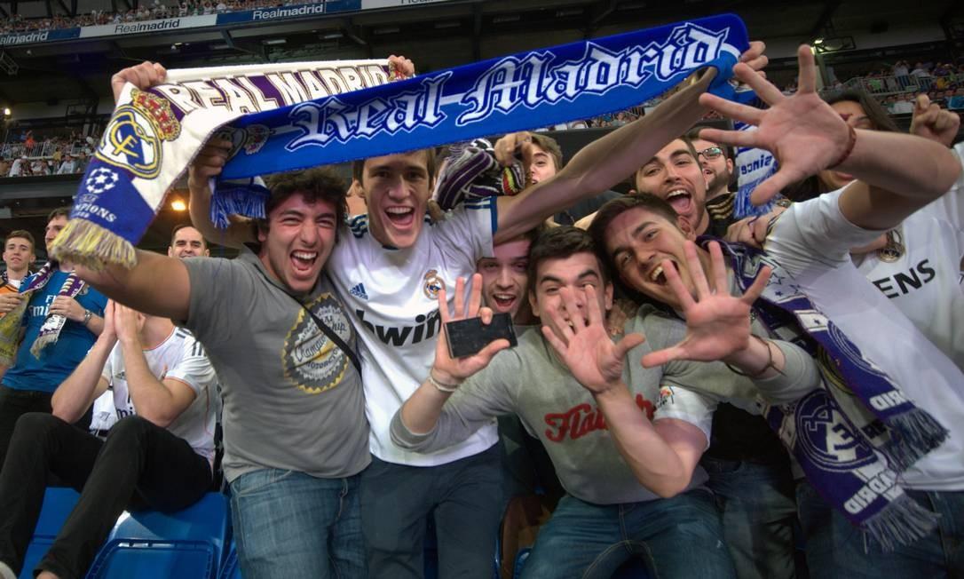 Os cachecóis de lã com o nome do clube se tornaram mania no futebol europeu. Eles servem para aquecer e exibir a paixão pelo clube como mostram os torcedores do Real Madrid na final da Liga dos Campeões Foto: CURTO DE LA TORRE / AFP