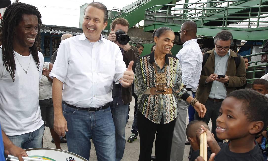O pré-candidato à presidência Eduardo Campos, acompanhado de Marina Silva, em visita ao AfroReggae, brinca com crianças do projeto Foto: Antonio Scorza / Agência O Globo