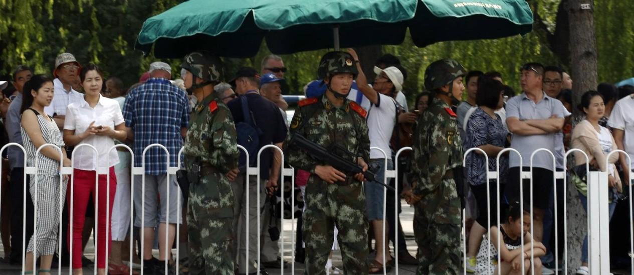 Soldados paramilitares fazem guarda em frente de visitantes em uma fila para passar por revistas de segurança antes de entrar na Praça da Paz Celestial, em Pequim Foto: Kim Kyung-Hoon / REUTERS