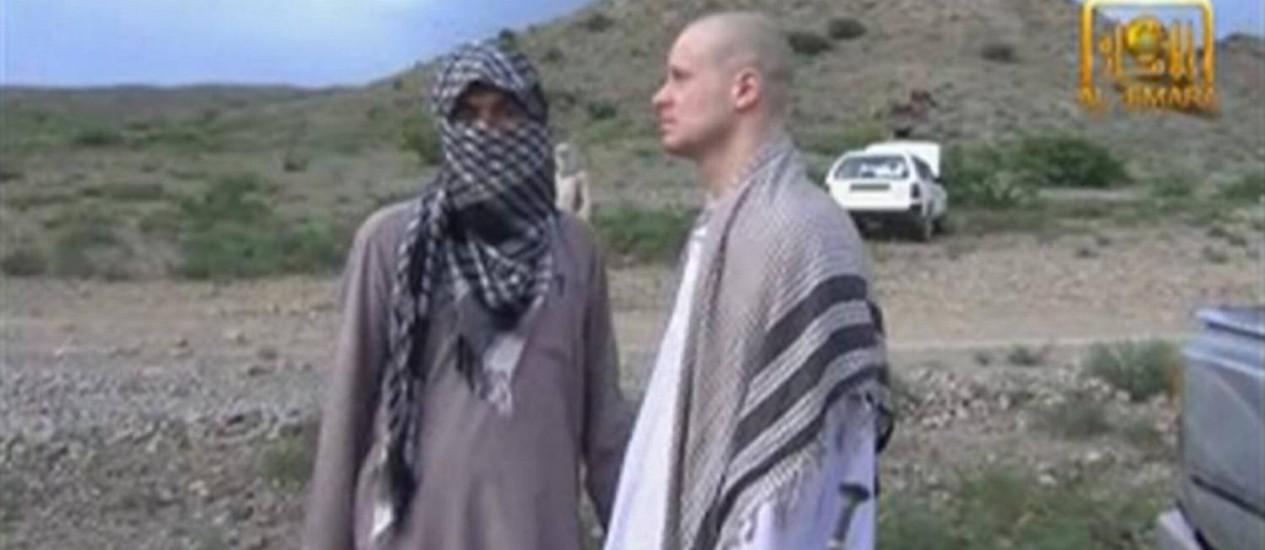 Imagem retirada de vídeo divulgado pelos talibãs mostra o sargento Bowe Bergdahl (à dir,) à espera de sua libertação na fronteira com o Afeganistão Foto: REUTERS TV / REUTERS