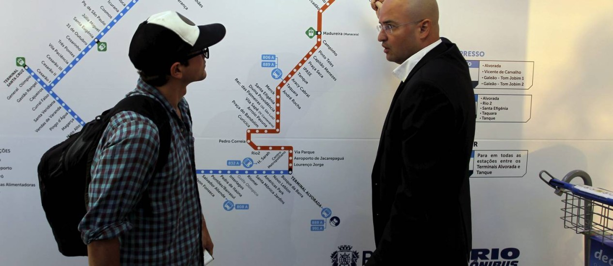 Secretário de Transportes, Alexandre Sansão, orienta turista californiano na estação do Galeão Foto: Gabriel de Paiva / O Globo