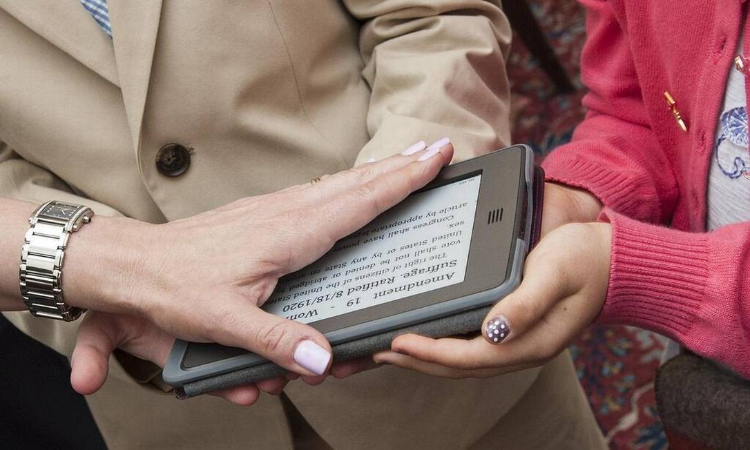 Com a mão sobre um kindle carregado com a Constituição americana, a embaixadora dos EUA na Suíça, Suzi LeVine, se tornou a primeira da História a jurar sobre um aparelho eletrônico Foto: / REPRODUÇÃO