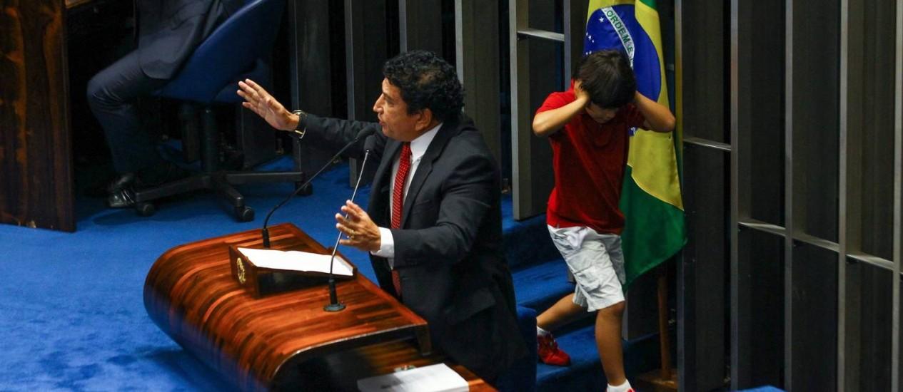 Durante o discurso do senador Magno Malta, contrário à lei, Enzo, neto do senador Renan Calheiros, presidente do Senado, passa correndo pela tribuna e tapa os ouvidos Foto: André Coelho