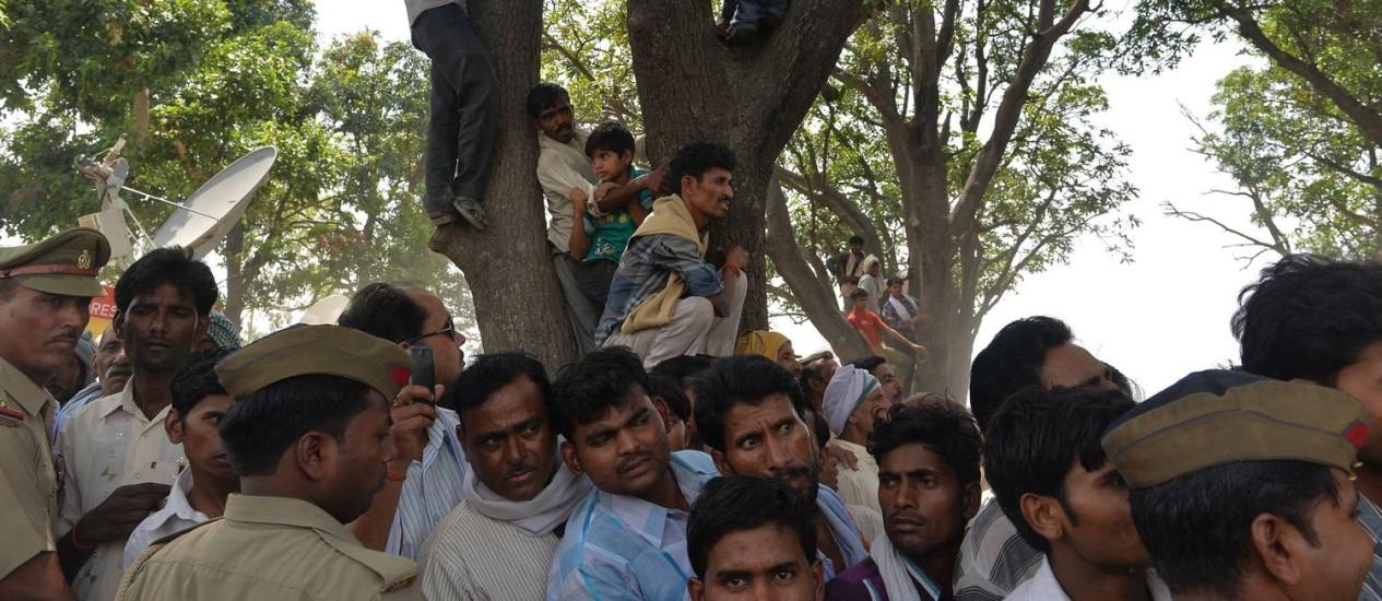 Indianos cercam a árvore onde duas adolescentes estupradas foram enforcadas: mulheres de castas mais baixas são as vítimas mais frequentes Foto: Chandan Khanna / AFP
