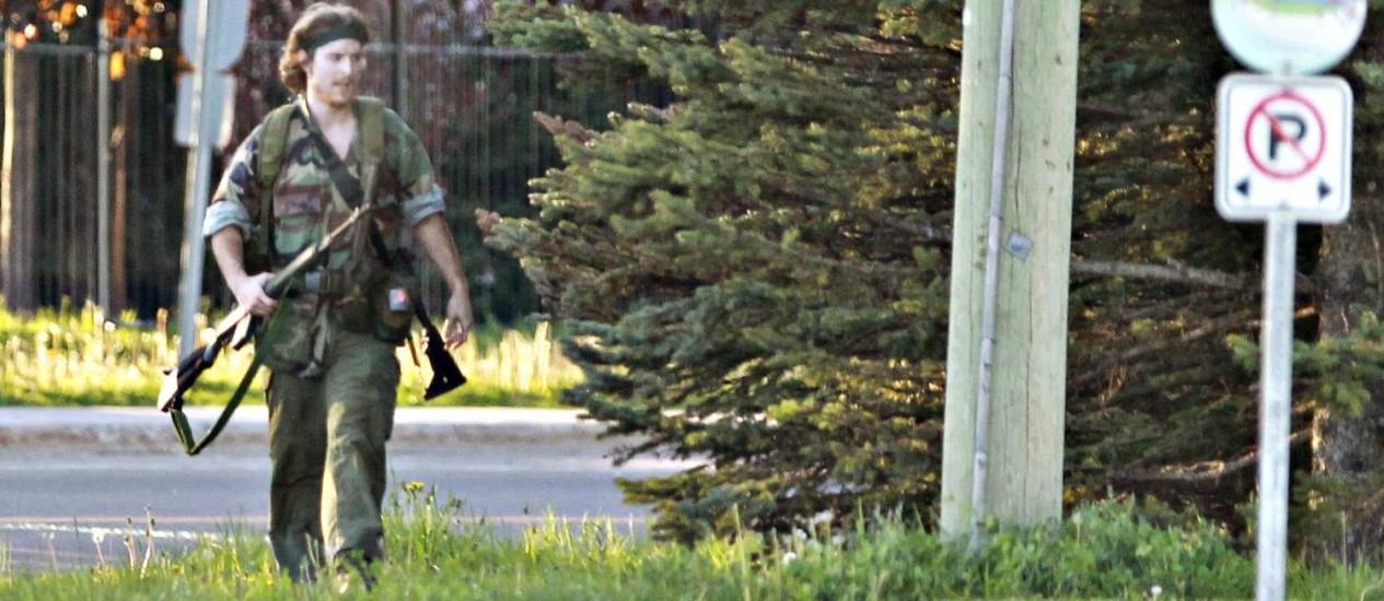 Suspeito anda armado em uma rua de Moncton Foto: TIMES & TRANSCRIPT / REUTERS