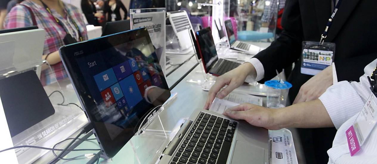 Visitantes interagens com modelos de PCs na Computex Foto: PICHI CHUANG / REUTERS