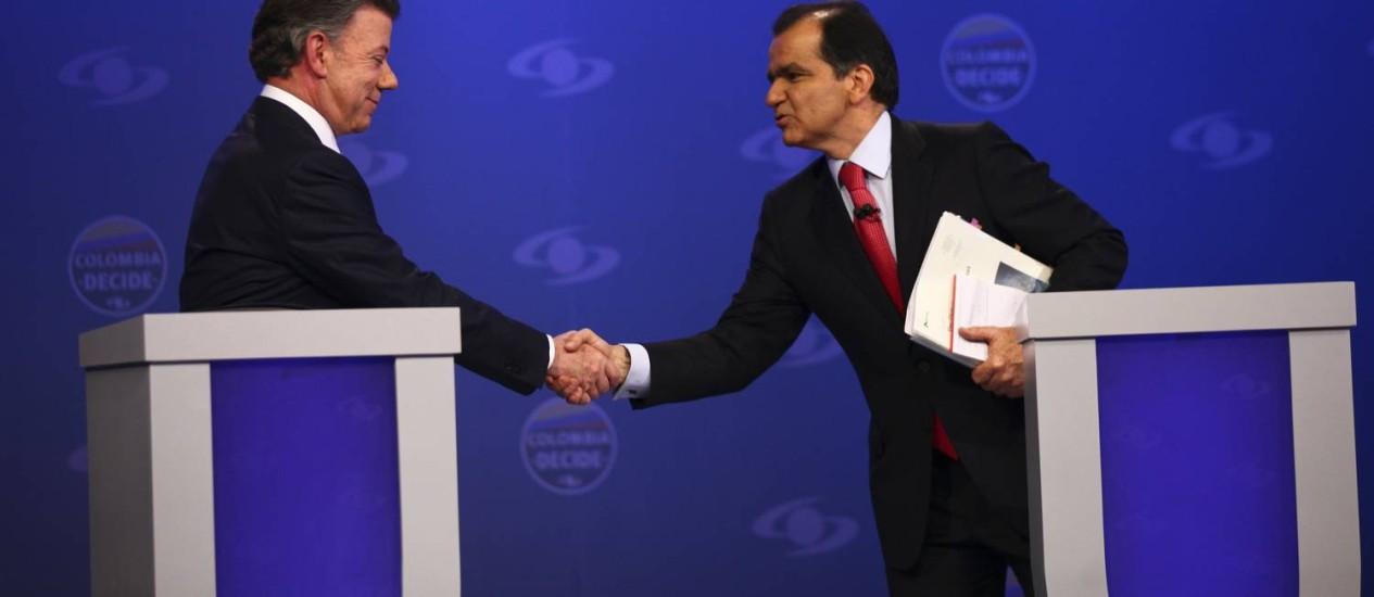 Presidente da Colômbia e candidato, Juan Manuel Santos (à esq.), e o candidato opositor Oscar Ivan Zuluaga apertam as mãos durante debate em um canal local, em Bogotá Foto: HANDOUT / REUTERS
