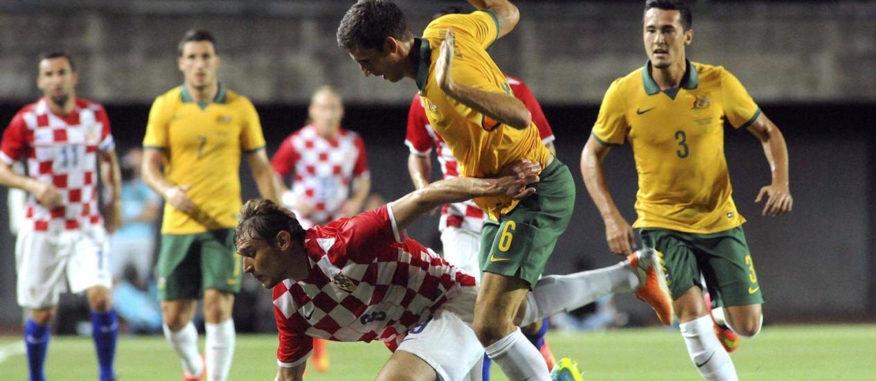 O croata Nikita Jelavic, à esquerda, divide a bola com o australiano Matthew Spiranovic Foto: STRINGER / REUTERS