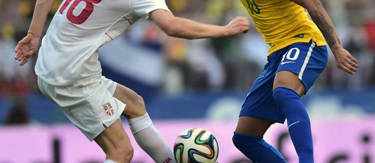 Neymar disputa a bola com o sérvio Dusan Basta no Morumbi. Amistoso foi considerado um bom teste para a estreia na Copa contra a Croácia Foto: NELSON ALMEIDA / AFP