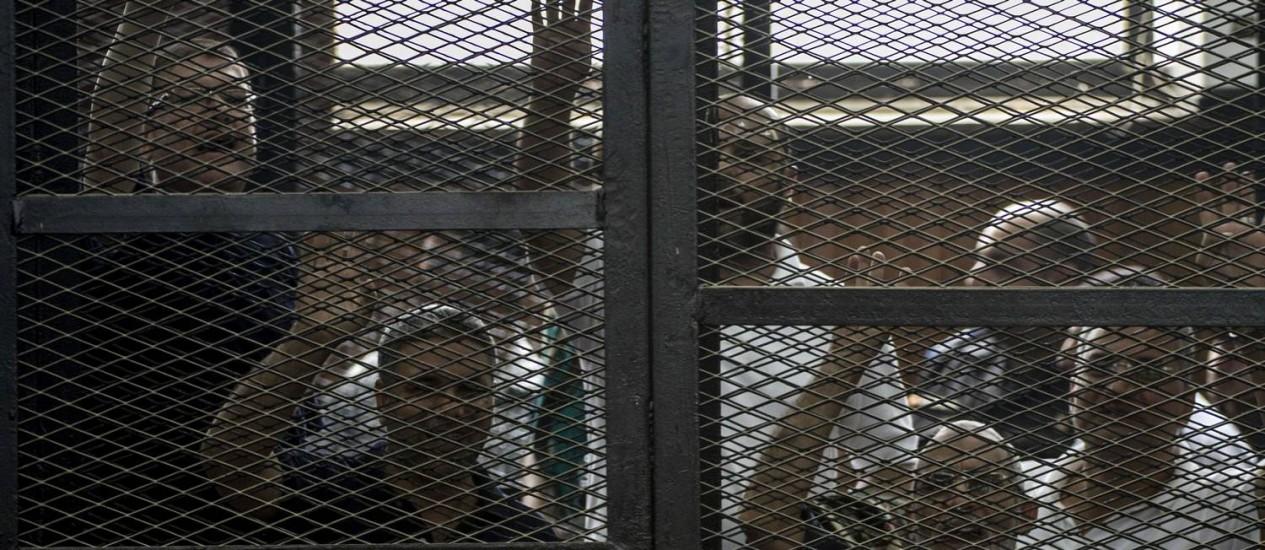 Líder da Irmandade Muçulmana, Mohamed Badie, protesta junto com outros réus durante julgamento de membros do partido Foto: KHALED DESOUKI / AFP