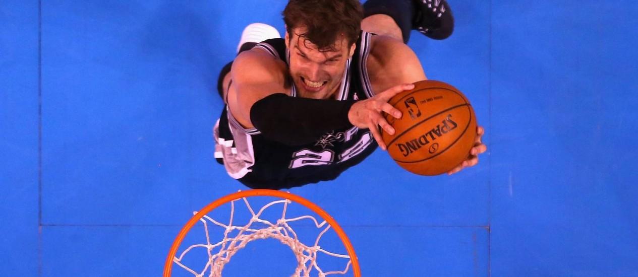 Tiago Splitter, do San Antonio Spurs, sobe para a enterrada na vitória de seu time sobre o Oklahoma City Thunder nas finais da Conferência Oeste da NBA Foto: RONALD MARTINEZ/AFP/27-05-2014
