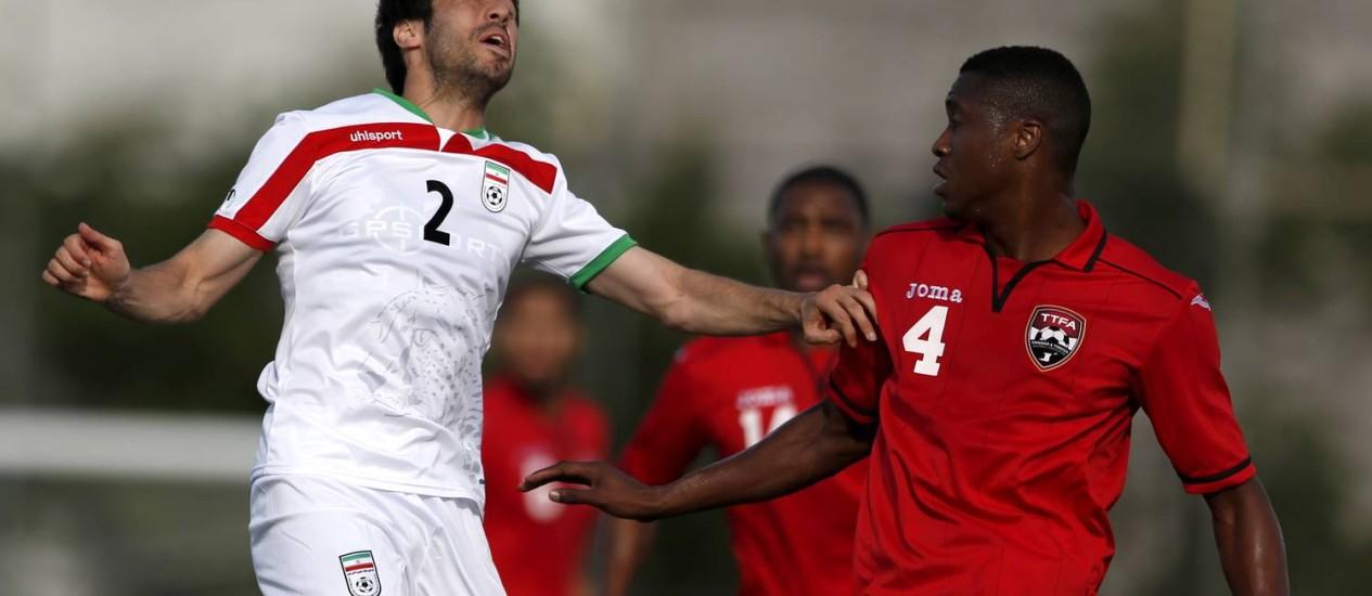 O lateral Khosrow Heydari disputa a bola com Sheldon Bateau, de Trinidad e Tobago. Iranianos encontraram dificuldades para derrotar a seleção caribenha no último amistoso antes da estreia contra a Nigéria, no dia 16 Foto: Julio Cortez / AP