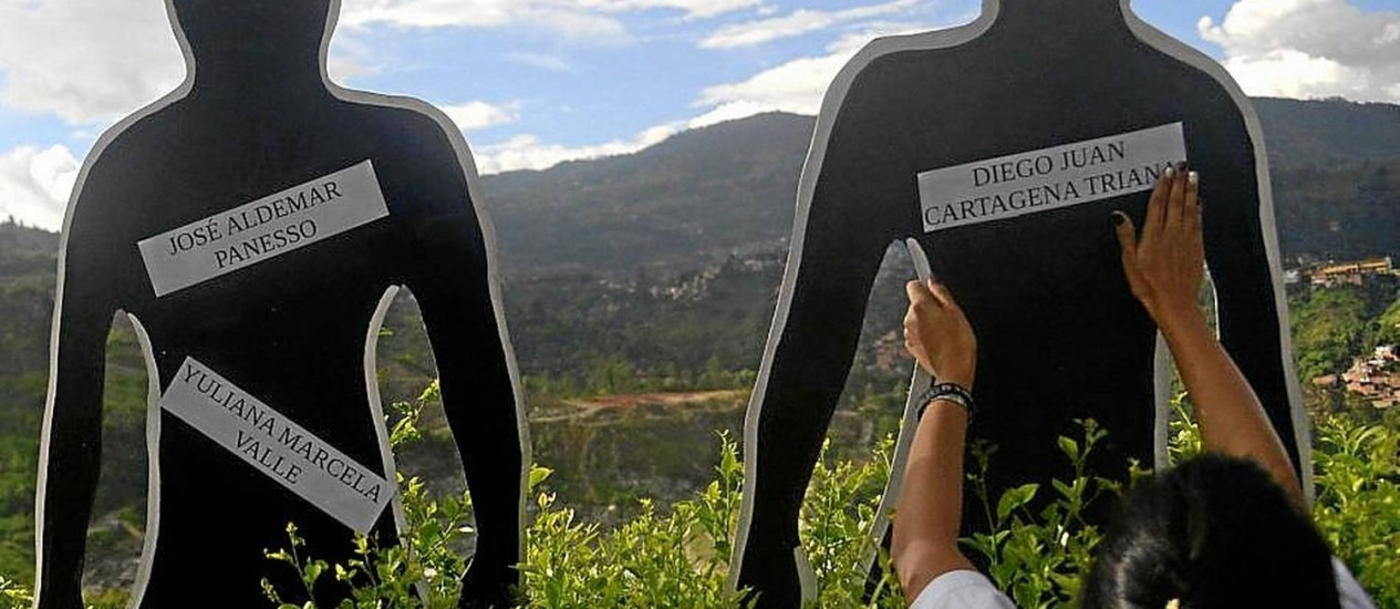 Parentes acrescentam nomes de desaparecidos durante vigília em Medellin Foto: RAUL ARBOLEDA/AFP