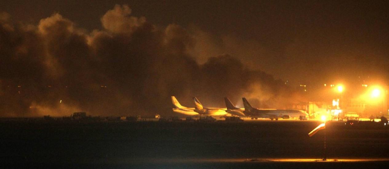 O fogo ilumina o céu sobre o aeroporto de Karachi, onde forças de segurança entraram em confronto com homens armados Foto: Fareed Khan / AP