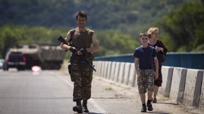 Separatista pró-Rússia caminha ao lado de sua família em uma ponte perto de um posto de controle nos arredores da cidade ucraniana de Luhansk Foto: SHAMIL ZHUMATOV / REUTERS