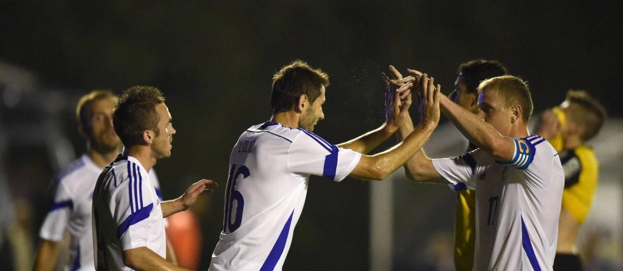 O bósnio Senad Lulic, ao centro, comemora um dos gols da seleção sobre o sub-21 do Santos Foto: YURI CORTEZ / AFP