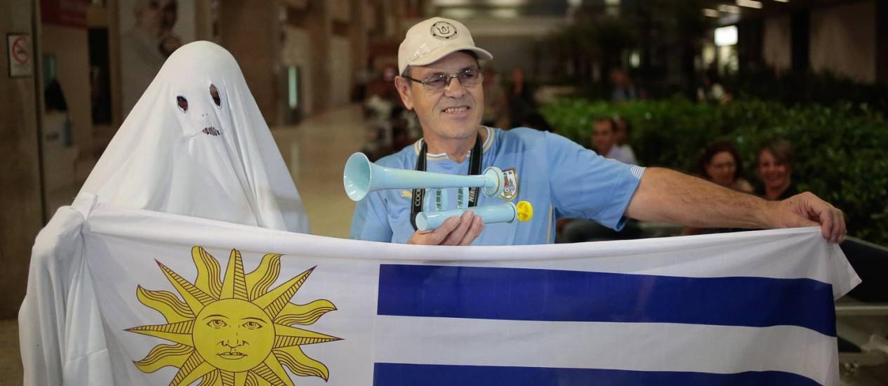 Fantasma aguarda desembarque da seleção uruguaia em Belo Horizonte. Seleção desmebarcou na pista e seguiu para Sete Lagoas sem passar pelo terminal Foto: Pedro Kirilos / Agência O Globo