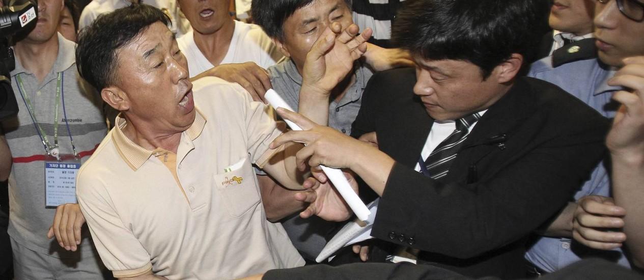 Familiares de vítimas do naufrágio enfrentam um segurança ao tentarem comparecer ao julgamento de tripulantes da balsa Foto: REUTERS