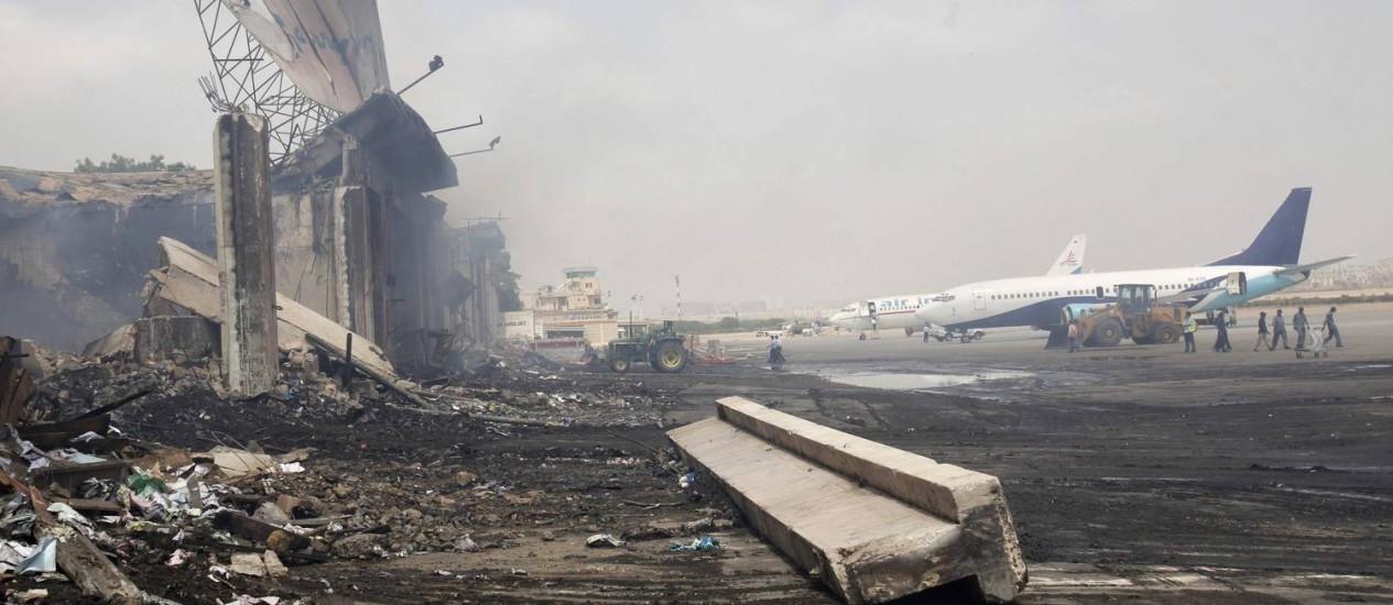 Aviões são vistos perto de um prédio destruído no aeroporto internacional de Jinnah Foto: ATHAR HUSSAIN / REUTERS