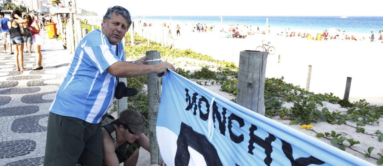 """Em Ipanema, Mario Fernandez pendurou uma bandeira da Argentina sobre os gradis que cercam a vegetação da praia: """"É para mostrar que estamos presentes"""" Foto: ANTONIO SCORZA / Agência O Globo"""